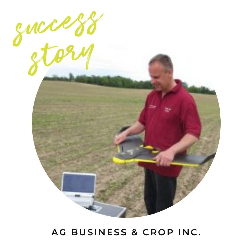 man flying drone over field of soy beans